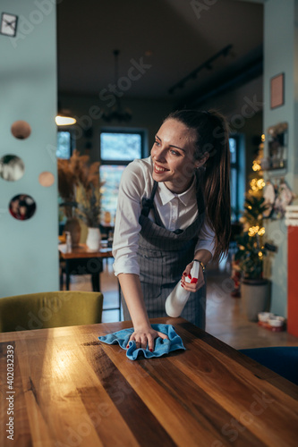 Fototapeta waitress cleaning tables in restaurant. obraz
