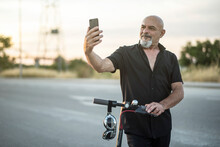 Attractive 60-year-old Mature Man On Electric Scooter Posing At Sunset For A Selfie