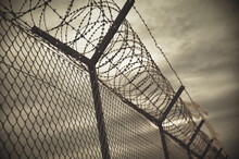 A Selective Focus Shot Of Fence With Barbed Wire