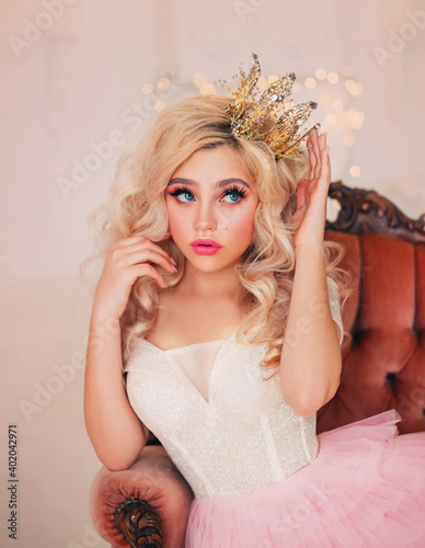 Portrait capricious princess girl. Blond hair. lady woman sitting in vintage armchair. Fairy tale white room. Woman Queen straightens gold crown on head with hand. surprised face, pink lips blue eyes