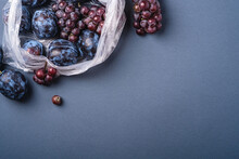 Fresh Ripe Plum Fruits And Grape Berries In Plastic Bag Package On Minimal Blue Grey Background, Top View Copy Space