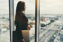 A Stately Mature Businesswoman With A Laptop In Hand Is Observing Cityscape Near The Window; A Charming Adult Woman Entrepreneur In A High-rise, With A Netbook, Pensively Looking On An Urban Landscape