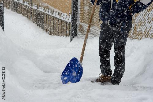 Fotografie, Obraz un uomo intento a spalare la neve durante una grande nevicata, nevicata recor ne