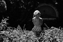A Grayscale Shot Of A Child Statue In The Garden
