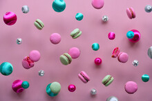 Levitation Of Macaroons, Creative Food Concept. Bold Vibrant Pink, Mint Green And Magenta Colors. Flying Tasty Macaroons, Mirror Disco Balls And Decorative Metallic Balls On Pink Paper Background.