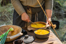 Scrambled Egg In Wooden Bowls Prepared By A Woman In Traditional Clothing. Homemade Food On The Table At Historical Reenactment Of Slavic Or Vikings Lifestyle From Around 11th Century, Cedynia, Poland