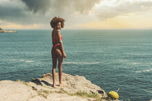 A Young Drop-dead Gorgeous African-American Woman In A Swimming Suit Is Standing Half-turned On A Cliff Of The Coast Of Tropical Resort Beach With A Fantastic View Of The Ocean And A Stormy Sunset Sky