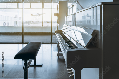 Fotografia A white glossy contemporary piano with an opened keyboard and a banquet nearby i