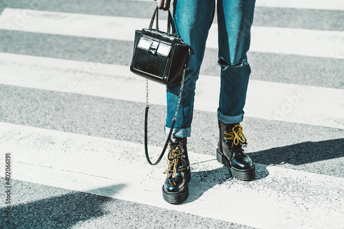 A close-up view of female legs in jeans and glossy boots with yellow laces - a w Fototapeta