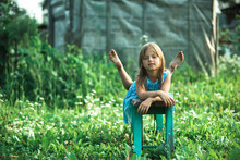 Little Girl Posing In The Yard Of A Country House.