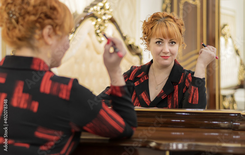 Fotografie, Obraz A young red-haired girl stands in front of a mirror, holds lipstick in her hand and looks intently into the camera