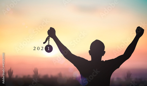 Fototapeta Success new year 2021 concept: Silhouette winner hand holding gold medal reward with text for 2021 against blurred sunset background obraz
