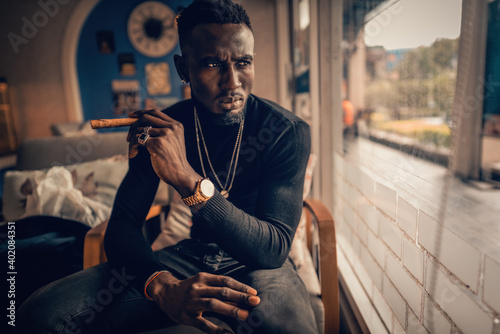 portrait of african american man holding cigar on hand in coffee shop