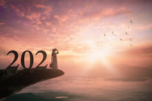 Success Businesswoman Of New Year 2021 Concept: Silhouette Traveler Woman With Text For 2021 Against On Mountain Sunset Background