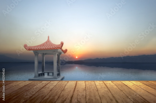 Fototapeta Wooden floor with a Chinese gazebo building on the lake