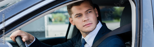 Businessman looking at window while driving car, banner.