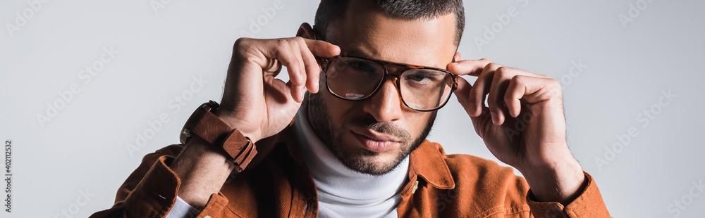 Fototapeta Stylish man adjusting eyeglasses and looking at camera isolated on grey, banner