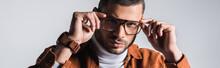 Stylish Man Adjusting Eyeglasses And Looking At Camera Isolated On Grey, Banner