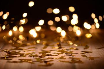 Confeti y luces desenfocadas en la mesa marrón, fantasía de fiesta