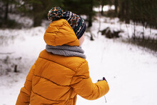 A Kid In A Yellow Down Jacket And A Hat Walks In The Forest In Winter. The Face Is Not Visible.