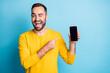Leinwandbild Motiv Photo portrait of man pointing finger display of smartphone copyspace winking isolated on vibrant blue color background