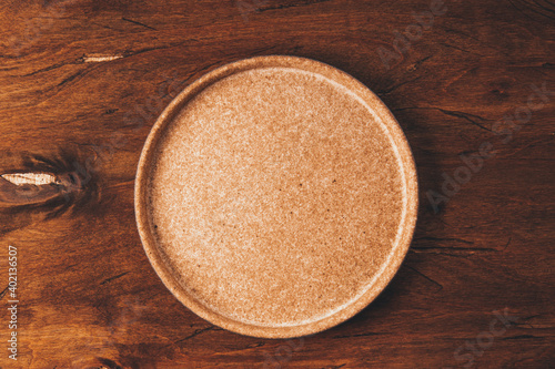 Tela Empty ceramic plate on brown wooden background top view