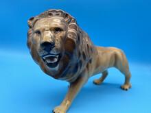 A Vintage Porcelain Lion Figurine On Blue Background