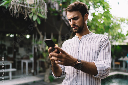 Serious young businessman reading unpleasant message on smartphone