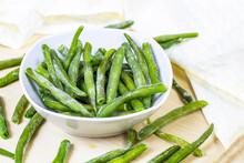 Frozen Green Beans Pods In White Bowl On Light Wooden Background.