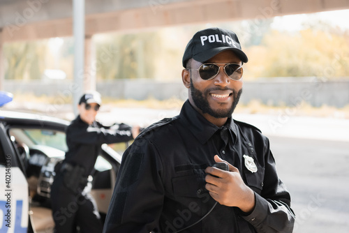 Fotografering happy african american police officer looking at camera while holding radio set on blurred background outdoors