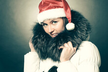 Beautiful Young Woman In Winter Coat And Santa Claus Hat.