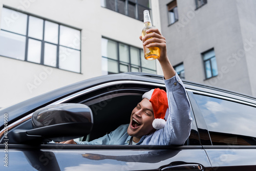 excited, drunk man in santa hat holding bottle of alcohol in raised hand while sitting in car.