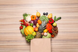 Fototapeta Kawa jest smaczna - Paper bag with assortment of fresh organic fruits and vegetables on wooden table, flat lay