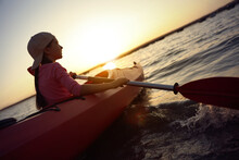 Little Girl Kayaking On River At Sunset. Summer Camp Activity