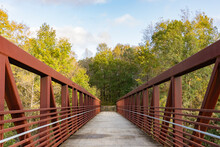 A Red Iron Pedestrian Bridge Leads Over A River Into The Woods On The Neuse River Greenway In Raleigh, North Carolina, USA