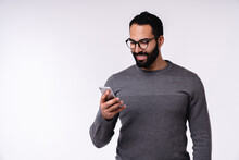 Nice-looking Young Arabian Man In Casual Clothes Using Mobile Phone Isolated Over White Background