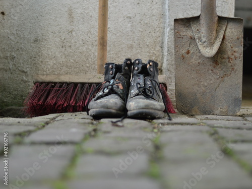 old worn painted work boots with a yard broom and a spade as symbol for cleaning Fototapete