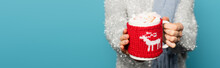 Close Up Of Cup With Marshmallows And Knitted Holder In Hands Of Blurred Woman On Background Isolated On Blue, Banner