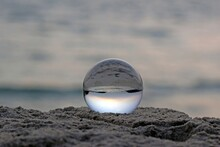 A Spherical Glass Ball Rests On Sand At A Beach Refracting The View Of Ocean And Blue Sky