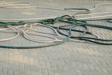 Tangled Hoses On Paving Stones In The City Of White And Green Color, Closeup View. Street Care In The City, Communications And Construction. Street Cleaning.