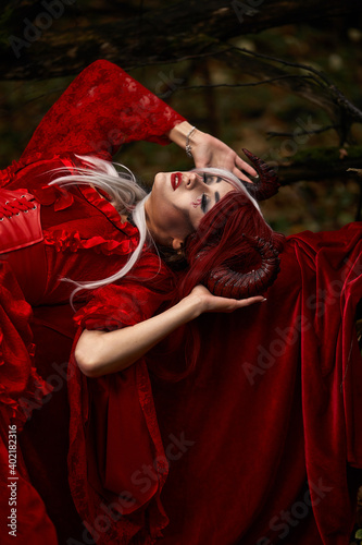 Fototapeta Maleficent Woman in Red Clothing and Horns in dark Forest