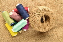 One Spool Of Jute Thread And Several Spools Of Colored Thread, Close-up, On Jute Fabric.
