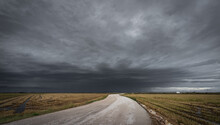 Curved Road Towards The Dark Stormy Clouds