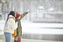 Young Couple In Warm Clothing Looking At Something Standing Outdoors When It's Snowing