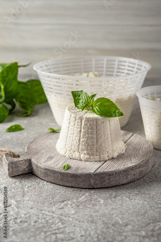 Fototapeta Homemade whey ricotta cheese or cottage cheese with basil ready to eat. Vegetarian healthy, nutritious diet food on a light background obraz