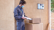 Messenger With Mask Delivers Packages To The Doorway Next To The Doorkeeper
