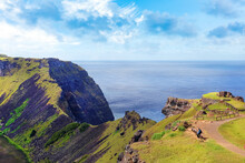View Of The Slopes Of The Rano Kau Volcano, On Easter Island, Covered By Green Vegetation And The Pacific Ocean Against A Blue Clear Sky.