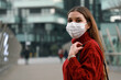 Leinwandbild Motiv Portrait of happy young confident young woman wearing protective mask outdoors and looking at camera. Smiling girl wearing surgical mask for virus protection standing in modern city street.