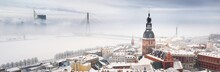 Panoramic Aerial View Of The Riga Old Town And Daugava River From St. Peter's Church In Winter. Morning Fog, Snow-covered Cable-stayed Bridge, Cathedral, Houses. Latvia. Landmarks, Sightseeing, Travel