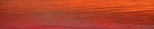 Epic Red Sunset Sky Reflecting In The Sea. Natural Pattern, Texture, Background, Panoramic View. Meteorology, Climate Change, Seasons, Hope, Peace Concepts. Water Surface, Ripple